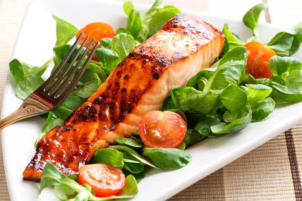 на гриле цельный лосось с овощами