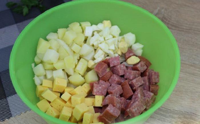 Смешивание ингредиентов салата из колбасы