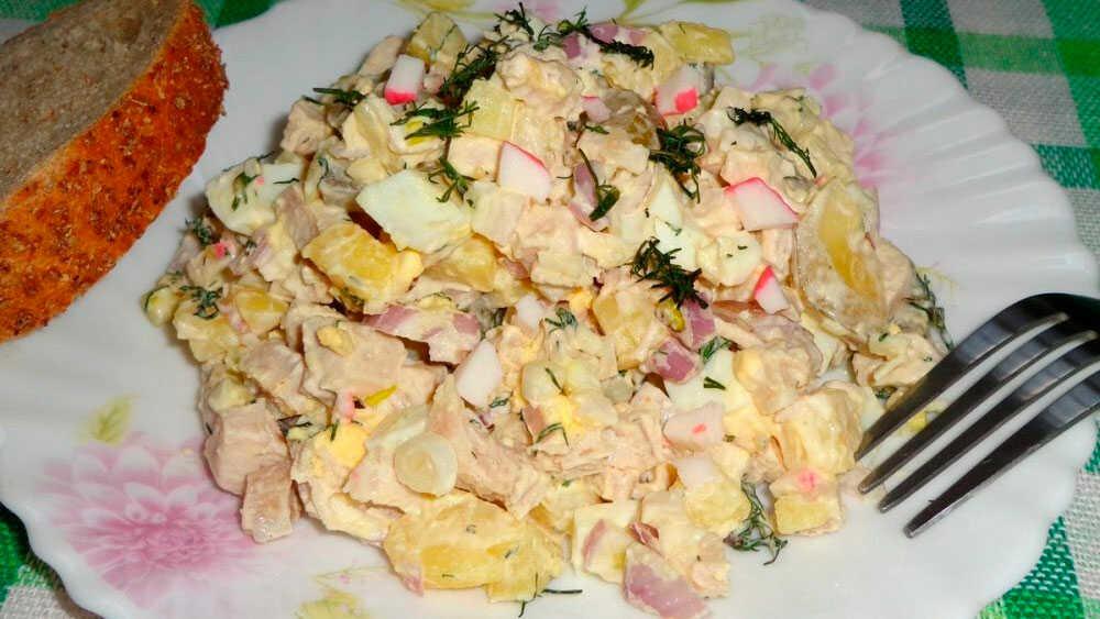 Салат с копченой курицей и крабовыми палочками на блюде