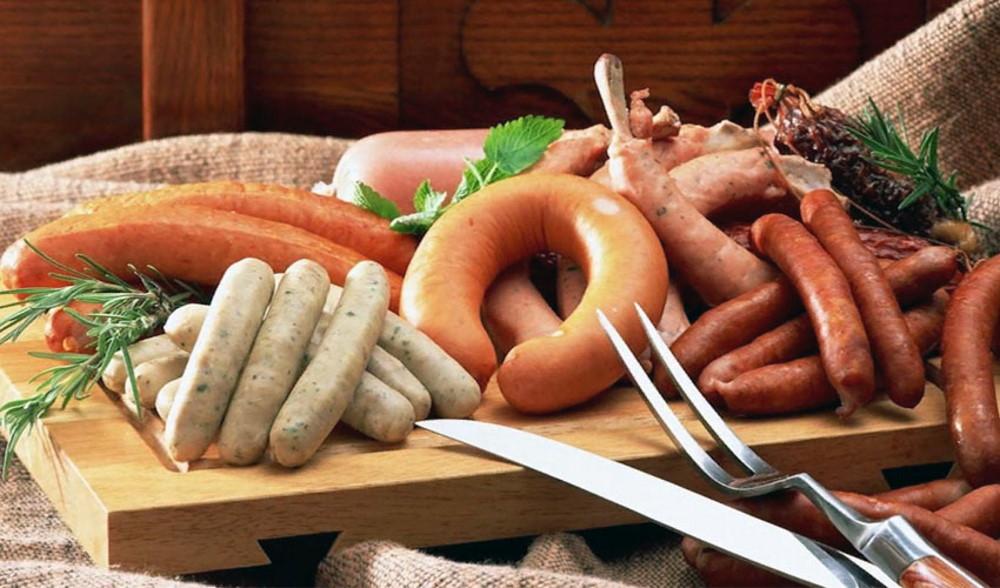 На деревянной доске лежит ассорти из сырых колбас и сосисок