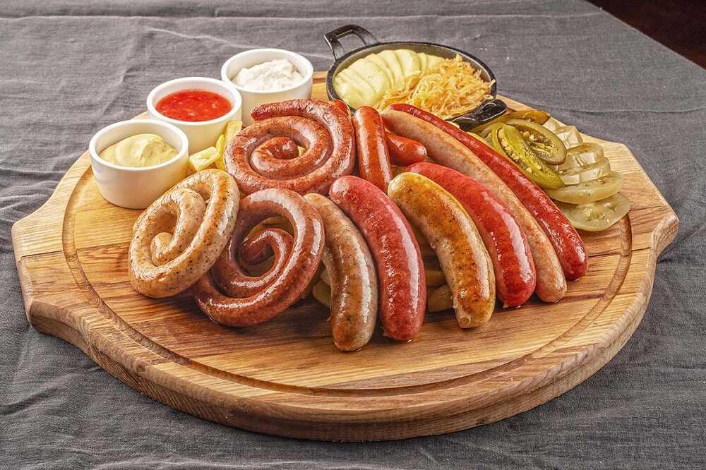 Красивая подача жареных колбасок на деревянной доске с тремя соусами т гарниром