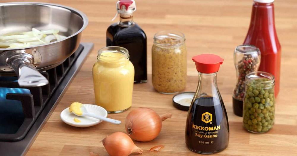 На столе выставлены соевый соус, горчица, каперсы, кетчуп, лук