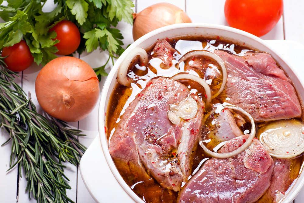 Куски свинины в маринаде из соевого соуса, лука и масла