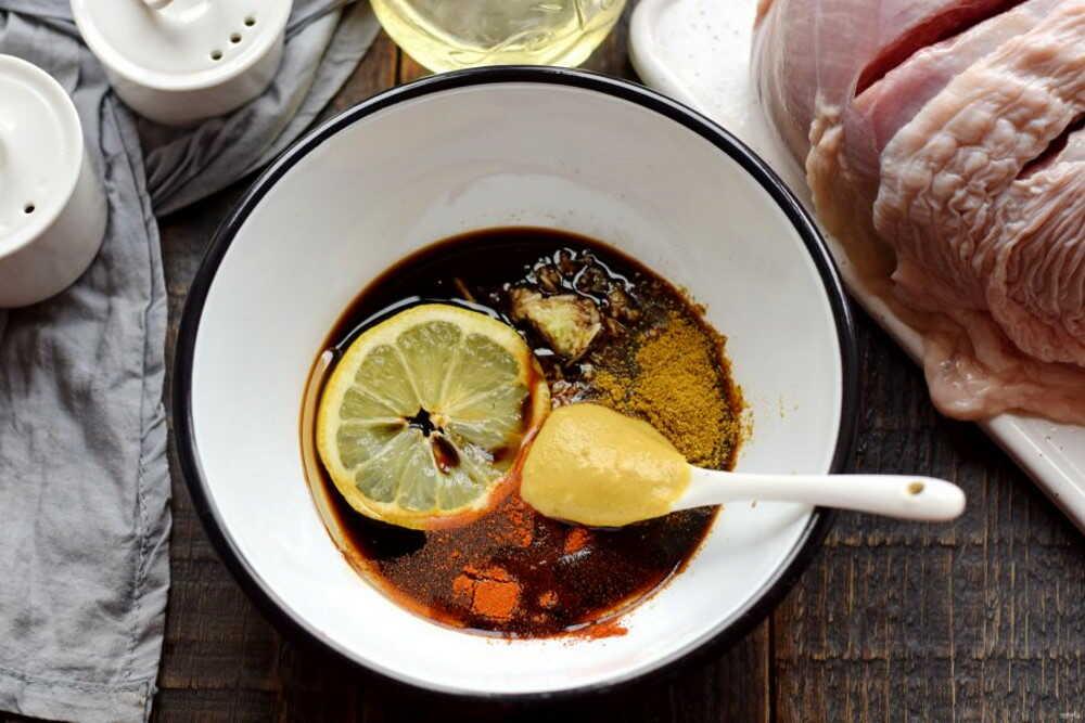 Белая миска с маринадом из соевого соуса, лимона и горчицы