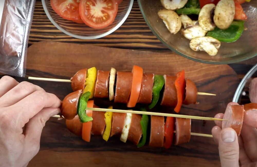 Повар нанизывает шашлычки на шпажки из колбасок и овощей