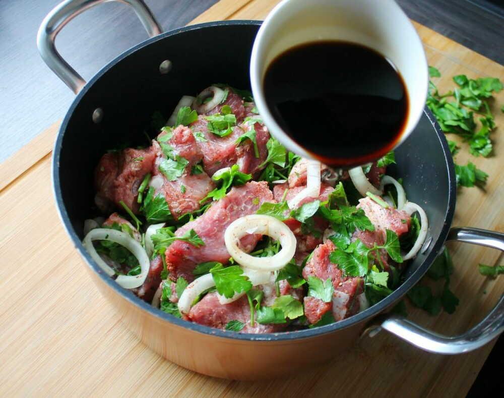 Кастрюля с кусками свинины и лука поливают соевым соусом