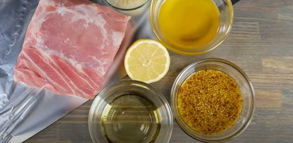 Нас толе расположен кусок свинины, горчица, лимон, мед, масло